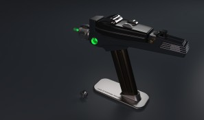 Phaser displayed on magnetic stand with tip glowing green and dilithium crystal inspection chamber door open